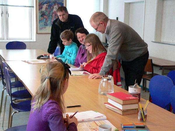 Børn, forældre og hjælpere hygger med lektier